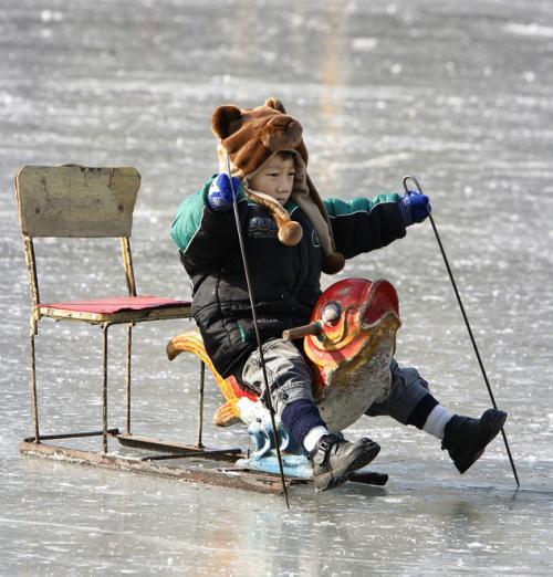 На фото изображен ребенок на специальных ледовых санках, озеро Хоухай, Пекин, 15 января 2008 года. И это не смотря н ... - Изображение 1