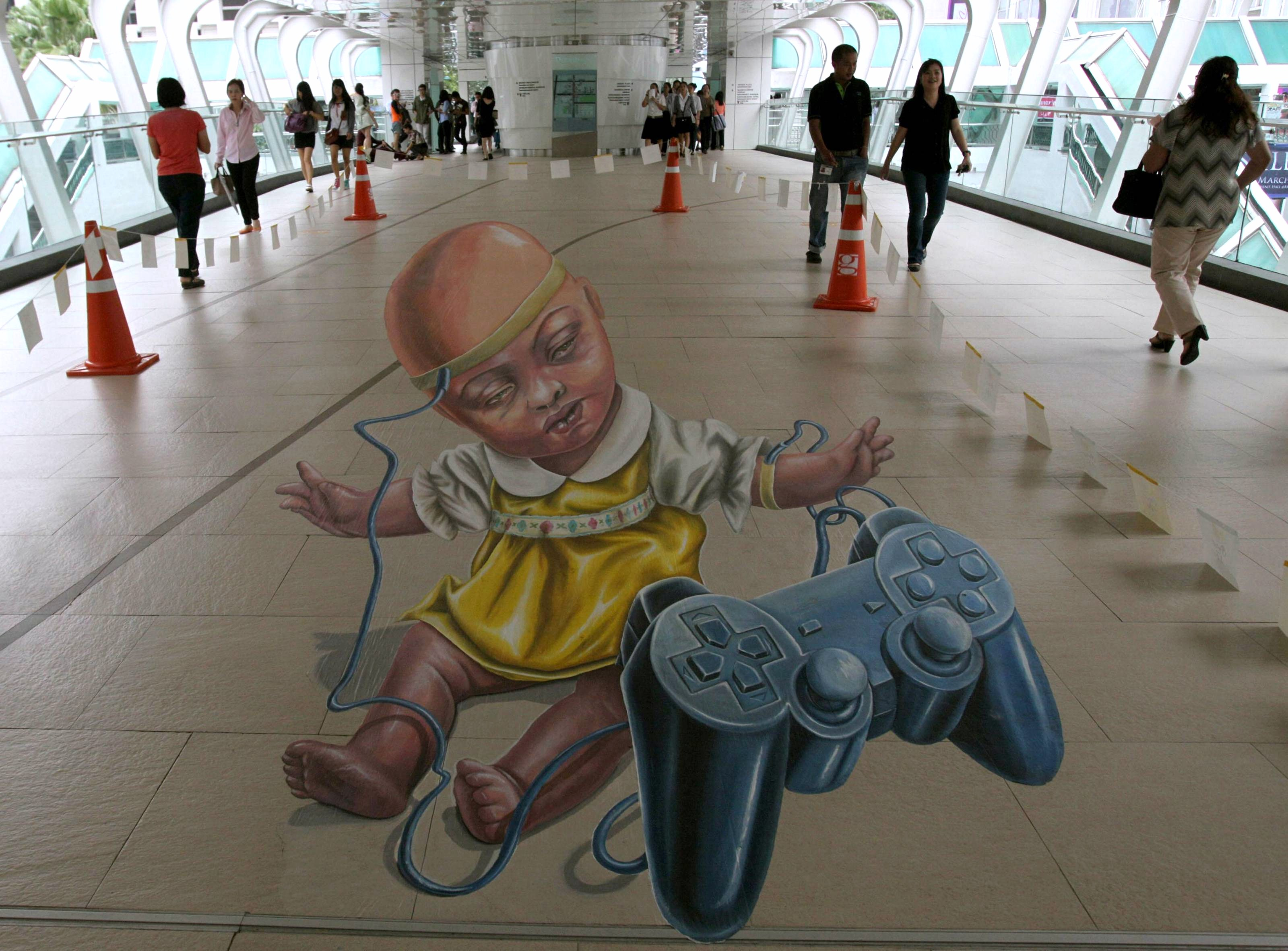 """Thai people walk beside a 3D street painting entitled """"Victim of Circumstance"""" by the Netherlands' Leon Keer during  .... - Изображение 1"""
